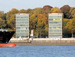 Herbst in Hamburg an der Elbe - Bürohäuser am Elbufer, im Hintergrund Bäume mit bunten Herbstfarben am Elbhang.
