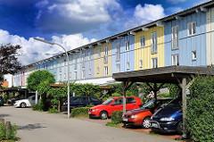 Carports mit Autos in einer Wohnstrasse von Hamburg Neuallermöhe; gelb und blau gestrichene Hausfassade.