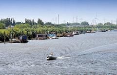 Spreehafen in Hamburg Wilhelmsburg / Kleiner Grasbrook - Wohnboote liegen am Ufer des Hafens - eins Sportboot / Schlauchboot mit Aussenbordmotor fährt Richtung Veddeler Kreuz, Müggenburger Zollhafen.