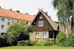 Einzelhaus mit Holzfassade und Reetdach; Wohnblocks in der Nachbarschaft - Fotografien der Archtitektur in Hamburg Eißendorf.