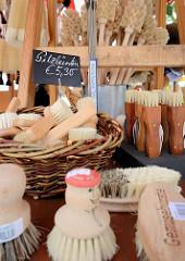 Biohof Gut Wulksfelde - Bauernmarkt. Aussteller präsentieren ihre Bioprodukte und Kunsthandwerk. Ein Bürstenmacher hat seine Besen und Bürsten zum Verkauf ausgelegt.