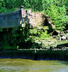 Alte, teilweise zerstörte Kaimauer mit Streichdalben auf der Wasserlinie im Hamburger Hafen.