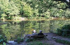 Teich im Quellental - ein Paar sitz auf einer Bank am Ufer und blickt über das Wasser.