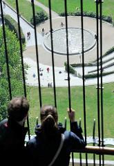 Blick durch die Gitterstäbe der Michelplattform zum Brunnen in der Grünanlage am Schaarmarkt.