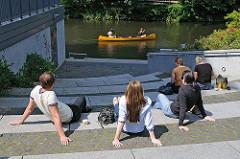 Winterhuder sitzen in der Sonne am Goldbekkanal Höhe Goldbekplatz - ein Kanu fährt vorüber.