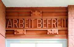 ARBEIT BEFREIT - Inschrift über dem Eingang eines Wohnhauses in Hamburg Barmbek Süd.