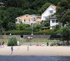 Elbstrand bei Hamburg Blankenese - Menschen liegen auf dem Sand in der Sonne oder sitzen auf einer Bank - im Hintergrund Gebäude am Strandweg im Hamburg Blankenese