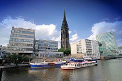 Theaterschiff am Nikolaifleet - Ausflugsschiff mit Fahrgästen / Touristen; Bürogebäude am Fleetufer; Turm der St. Nikolaikirche.