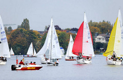Segelboote auf dem Hamburger See Aussenalster - Segelregatta; Motorboote DLRG - am Ufer Herbstbäume.