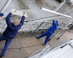 Abbau des Zollzaun am Zollkanal Kannengiesserbrücke / Brook; zwei Arbeiter nehmen das herausgetrennte Teilstück des Zollzauns heraus. 2003 wird die der Hamburger Stadtteil Hafencity mit der Speicherstadt aus der Freizone / Freihafen ausgegliedert.