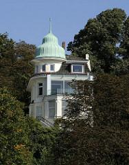 Villa mit kupfergedecktem Giebelturm zwischen Bäumen am Elbhang, hoch über der Elbe an der Elbchaussee.