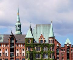 Mit Efeu bewachsene Fassade in der Hamburger Speicherstadt - Giebeltürme mit Kupfer gedeckt - Dachwinden und Türen - im Hintergrund die Turmspitze der St. Katharinenkirche.