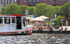 Schiffsanleger Jungfernstieg - ein Fahrgastschiff kommt von seiner Alsterrundfahrt und legt am Jungfernstieg an - HamburgerInnen sitzen am Ufer und lassen die Beine ins Wasser baumeln.