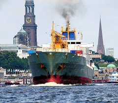 Der Frachter CHIQUITA BREMEN läuft aus dem Hamburger Hafen aus - Qualm steigt aus seinem Schornstein - im Hintergrund die St. Pauli Landungsbrücken sowie die St. Michaeliskirche und die St. Petrikirche.