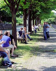 Uferpromenade mit Bäumen am Kanalufer des Mittelkanals in Hamburg Hammerbrook - Angestellte der umliegende Büros sitzen auf Bänken im Schatten der Bäume.