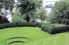 Heckentheater im Römischen Garten am Elbhang von Hamburg Blankenese - auf der Elbe fährt ein Containerfrachter zum Hafen von Hamburg.