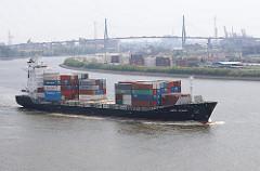 Ein Containerschiff kommt aus der Süderelbe und fährt in die Elbe ein - am Ufer ein Containerlager auf Waltershof und im Hintergrund eines der Wahrzeichen Hamburgs, die Köhlbrandbrücke.