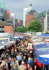 Blick über das Fischmarktgelände von Hamburg Altona - dicht stehen die Marktbuden beieiander - die Marktbesucher strömen bei Sonnenschein über den Markt.