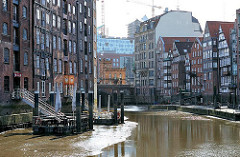 Ebbe im Nikolaifleet - die Pontons, die für die Aussengastronomie eines Restaurants genutzt werden sind trocken gefallen. Im Hintergrund die Hohe Brücke und Durchfahrt zum Zollkanal.