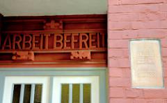Mauerplakette / Erinnerungsinschirft Zerstört 1943 - 1951 aufgebaut - ARBEIT BEFREIT - Inschrift über dem Eingang eines Wohnhauses in Hamburg Barmbek Süd.