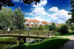 Fleet / Entwässerungsgraben in Hamburg Neuallermöhe - Holzbrücke über das Fleet, Wohngebäude am Ufer.