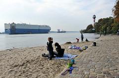 Strandleben in Hamburg Rissen - Sandstrand an der Elbe - ein Stückgutfrachter - Roll  on Roll off RoRo Frachter auf der Elbe vor Wittenbergen.