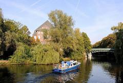 Ein Polizeiboot der Hamburger Wasserschutzpolizei fährt vom Kuhmühlenteich in den Eilbekkanal ein. Hinter Bäumen ist das Schumacher-Gebäude der Hamburger Hochschule für Bildende Künste zu erkennen.