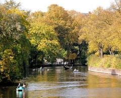 Kanalisierte Alster - Ruderboote und Tretboote auf dem Wasser in der Herbstsonne - Bäume mit Herbstblättern am Ufer.