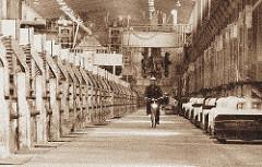 Werkshalle der Aluminumwerke in Hamburg - ein Arbeiter fährt auf einem Fahrrad durch eine der Werkshallen der Aluminiumhütte.
