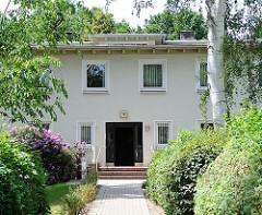 Hauseingang - blühender Rhododendron; Gartensiedlung Mechelnbusch - erbaut 1949, Architekten Heinz Graaf und Max Corleis. Wohnhäuser mit Parklandschaft, 200m² Garten für jeden Mieter - Baudenkmale in Hamburg Rissen