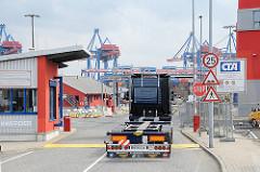 Ein leerer Sattelschlepper fährt durch die Einfahrt des Altenwerder Containerterminals um seine Containerladung abzuholen.