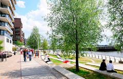 Promenade in der Hamburger Hafencity - Vacso da Gama Platz, Grasbrookhafen - Passanten flanieren - Ruhe auf Bänken am Wasser.
