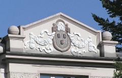 Giebelschmuck eines Gründerzeithauses. Stuck Ornamente, Wappen farblich abgesetzt.