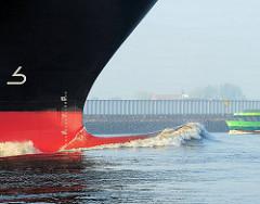 Schiffsbug in Fahrt - Symbol des Wulstbugs an der schwarzen Bordwand - rote Wasserlinie.