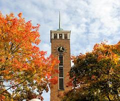 Kirchturm der Frohbotschaftskirche in Hamburg Dulsberg zwischen Herbstbäumen - Blätter herbstlich rot, braun und gelb gefärbt.