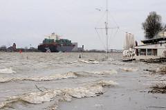 Wellengang am Strand von Hamburg Oevelgönne - das Hochwasser der Elbe reicht bis an die Strandperle heran - auf der Elbe ein Containerschiff.