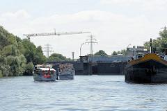 Sportboote warten vor der alten Ernst August Schleuse in Hamburg Wilhelmsburg - die Tore zur Schleusenkammer öffnen sich gerade - im Hintergrund ein Baukran der Baustelle für die neue Schleuse am Klütjenfelder Hauptdeich.