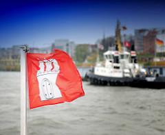 Die Fahne der Hansestadt Hamburg weht im Wind auf der Elbe - Schlepper am Ponton vor Hamburg St. Pauli.