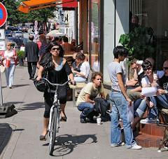 Sommertag in Hamburg Winterhude - die Menschen sitzen auf dem Mühlenkamp und geniessen die Sonne.