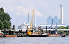 Bilder aus dem Stadtteil Hamburg Rothenburgsort - Hafenanlage beim Entenwerder Elbpark - Arbeitsschiffe am ehem. Zollanleger - Industriearchitektur mit Schornsteinen des Heizkraftwerks Tiefstack in der Billwerder Bucht.