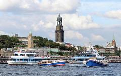 Barkassen und Fahrgastschiffe auf der Elbe vor den Hamburger St. Pauli Landungsbrücken - im Hintergrund der hohe Kirchturm des Hamburger Wahrszeichens, der Michel.