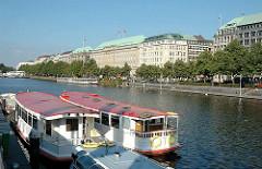 Fahrgastschiffe liegen am Anleger Jungfernstieg - am Ballindamm stehen hohe Kontorhäuser - Verwaltungshäuser im Stil des Historismus.