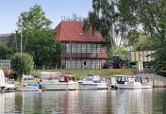 Sportboothafen in Hamburg Moorfleet an der Dove Elbe; historisches Hufnerhaus am Moorfleeter Deich.