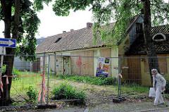 Rückseite von Abrisshäusern in der von Sauer Strasse in Hamburg Bahrenfeld; das Gelände ist mit einem Bauzaun abgesperrt.