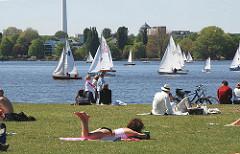 Segelboote auf der Hamburger Aussenalster - sonnenhungrige Hamburger und Hamburgerinnen sitzen und liegen auf der Wiese am Ufer des grossen Hamburger Sees.