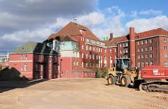 Baustelle beim Gebäude des ehemaligen Amts für Strom und Hafenbau - Bagger stehen auf der aufgeschütteten Sandfläche - Baubeginn für das Überseequartier.