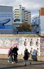 Bauzaun mit Plakatwerbung - im Hintergrund Wohnhäuser und Bürohäuser sowie die  Minarette der Centrums Moschee in Hamburg St. Georg - Merkez Camii Moschee;  Kunstprojekt von Oran Burchardt + der Leitung der Moschee, 2009 umgesetzt.