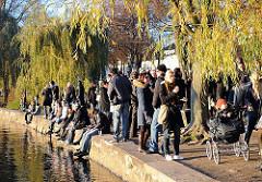 Herbstliche Abendstimmung am Alsterufer bei der Alsterperle - Gäste stehen in der Abendsonne oder sitzen am Wasser der Alster.