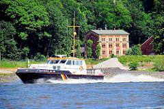 Boot der Schifffahrtspolizei Niederelbe vor dem Ufer von Hamburg Blankenese - im Hintergrund das historische Gebäude / Industriearchitektur der Altonaer Wasserwerke
