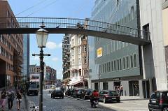 Bilder aus der Grossen Elbstrasse vom Hamburger Stadtteil Altona Altstadt. Eine Fussgängerbrücke verbindet die Gebäude beiderseits der Strasse.